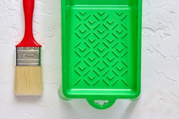 白いコンクリートに赤いハンドルと緑のペイントトレイ付きブラシ。家の改修のためのツールとアクセサリー。上面図 Premium写真
