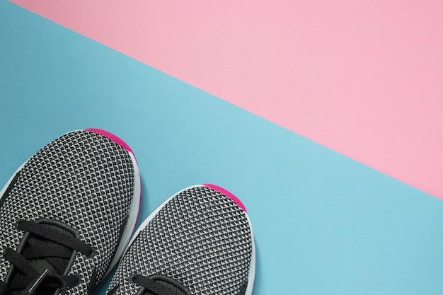 マルチカラーの表面にある一対のスポーツシューズ。コピースペースでピンクとブルーのパステル調の背景に新しい黒と白の女性スニーカー。平面図、平置き Premium写真