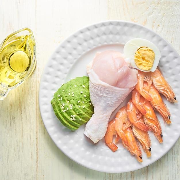 ケトジェニック食品-鶏肉、エビ、卵、アボカド、エキストラオリーブオイルの平面図。健康食品のコンセプト Premium写真