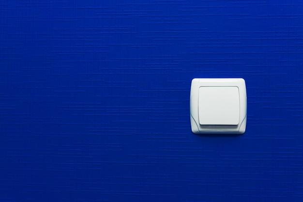 水色の壁の背景の光スイッチ。インテリア・デザイン。最小限のスタイル。 Premium写真