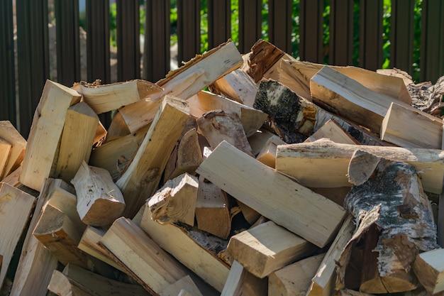 乾いた薪の積み重ね。家を暖めるために冬に備えて。 Premium写真