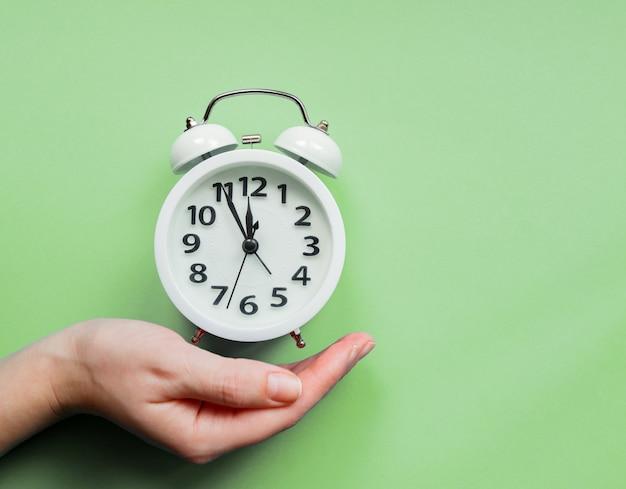 パステルグリーンの背景に目覚まし時計を持っている女性の手。 Premium写真