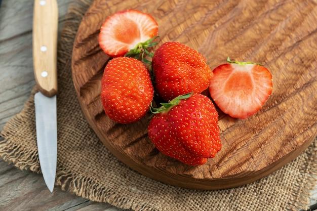 Закройте целую и нарежьте свежую красную клубнику на дубовой разделочной доске с ножом Premium Фотографии
