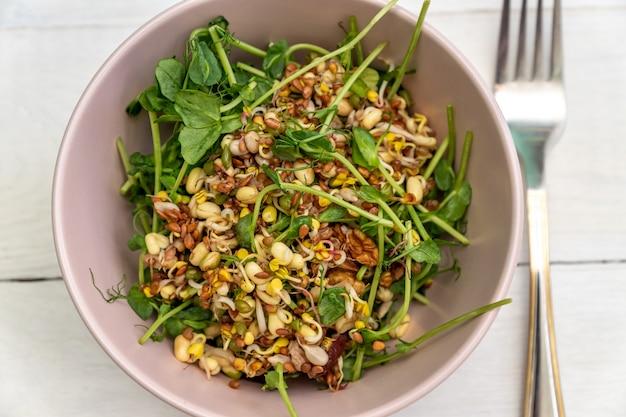 Веганский полезный салат из гороха с зелеными ростками и проросшей фасолью в розовой миске Premium Фотографии