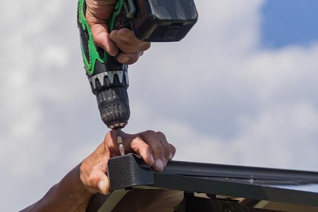 男性の手で電動ドライバー。金属製の構造を組み立てるハンドツールを持つ労働者 Premium写真