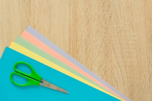 木製のテーブルに色とりどりの紙とはさみのトップビュー Premium写真
