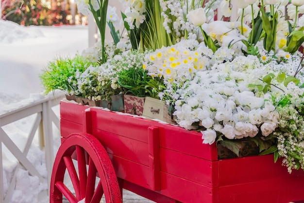 咲く人工花でいっぱいの木箱と赤い木製手押し車。 Premium写真
