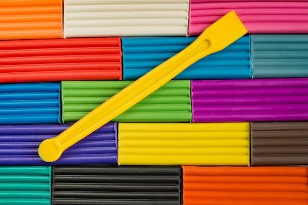Радужные цвета лепки из глины. разноцветный пластилин баров фон с желтой пластиковой палочкой. Premium Фотографии