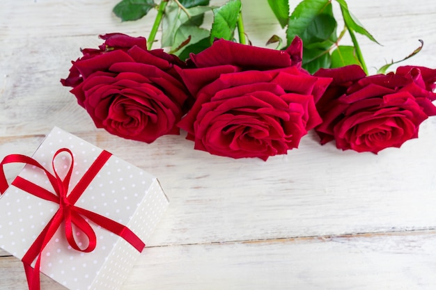 Бежевый горошек подарочная коробка с красной лентой лук и красивые красные розы на деревянных фоне. Premium Фотографии