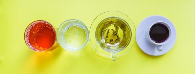 さまざまな飲み物-黄色の背景にコーヒー、炭酸水、リンゴジュース、緑茶を飲むのトップビュー。健康的な生活とダイエットのコンセプト Premium写真