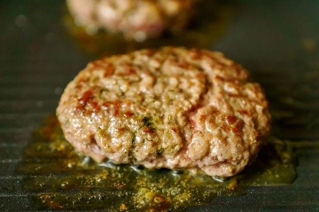 自宅のグリルでスパイスと肉のハンバーガーを調理します。クローズアップ、セレクティブフォーカス Premium写真