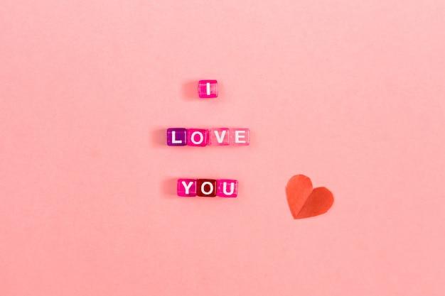 文字でカラフルなキューブビーズで作られた碑文が大好きです。コピースペースでお祝いピンクの背景概念 Premium写真