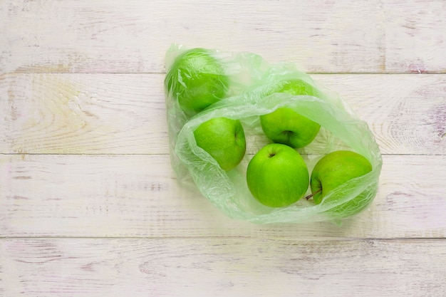 木製のテーブルのビニール袋に新鮮な青リンゴ。プラスチックの非生態的使用の環境概念 Premium写真