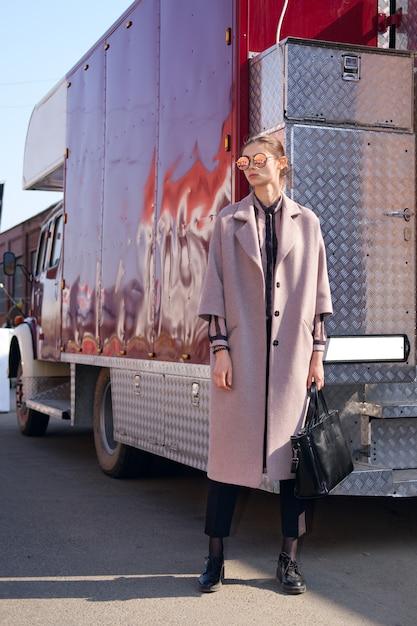 太陽を楽しんでいる固定されていないコートの少女。それを反映している通りでミラーサングラス。 Premium写真
