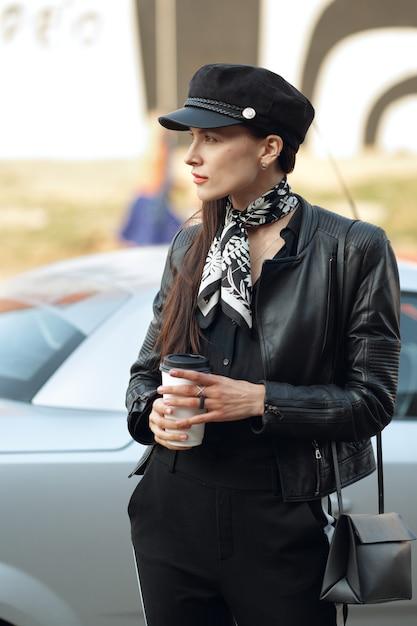 Привлекательная девушка, прогуливаясь по улице с чашкой кофе Premium Фотографии