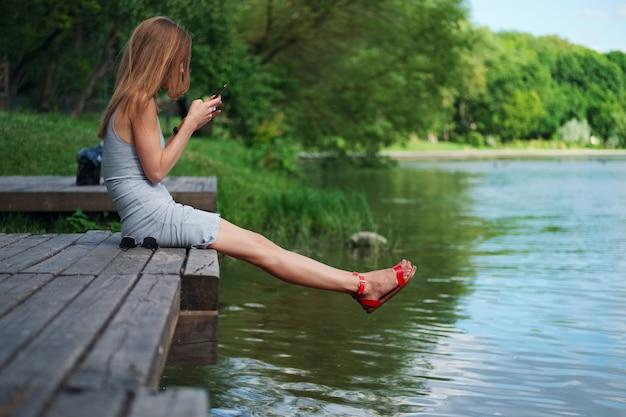 川の土手とメッセージングの木製の桟橋に座っている女の子の側面図。風に吹かれて髪の美しい女性。 Premium写真