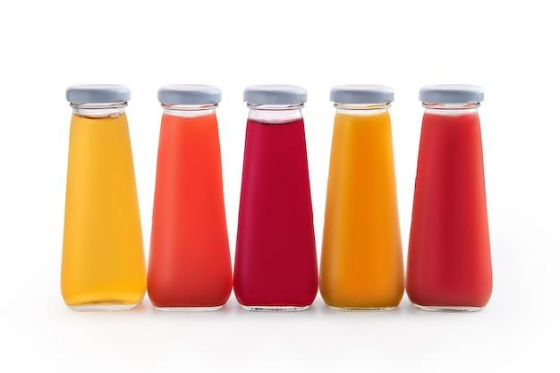 白で隔離される小さなガラス瓶に各種ジュース Premium写真