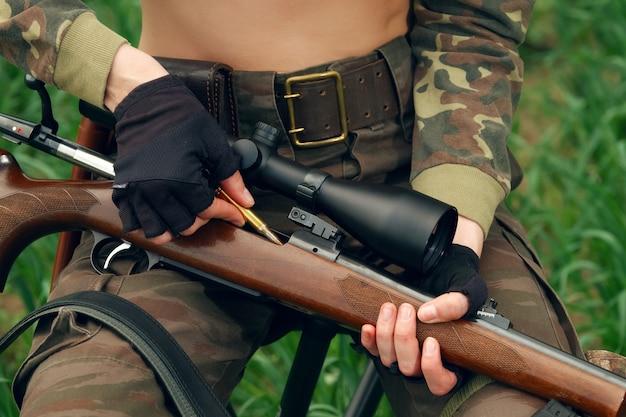 Охотник заряжает пулю в карабин оптическим прицелом Premium Фотографии
