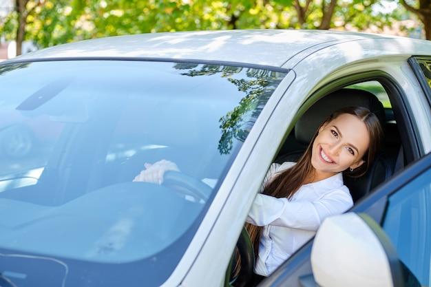 車のホイールの後ろに美しい笑顔ブルネットの少女 Premium写真