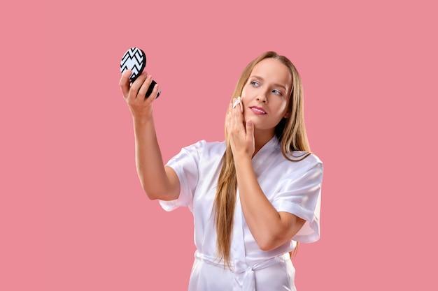スポンジパッドで顔から化粧を削除するきれいな女の子。 Premium写真