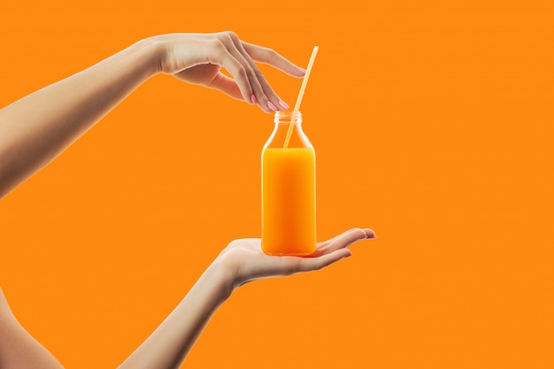 新鮮なデトックスオレンジジュースのストローでボトルを保持している女性の手 Premium写真