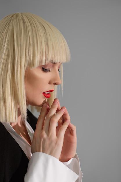 Красивая фотомодель в белом парике молится перед подиумом Premium Фотографии