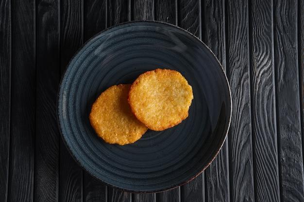 暗い木製のテーブルの上のフライドポテトのパンケーキの部分 Premium写真
