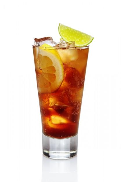 コーラ、氷、レモン、ライムのハイボールグラスを白で隔離されるカクテルウイスキー。 Premium写真