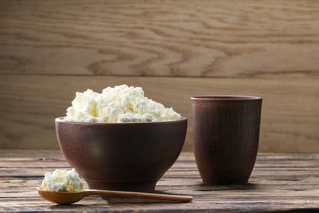 素朴な木のミルクのガラスと木のスプーンで粘土ボウルで新鮮なカッテージチーズ Premium写真