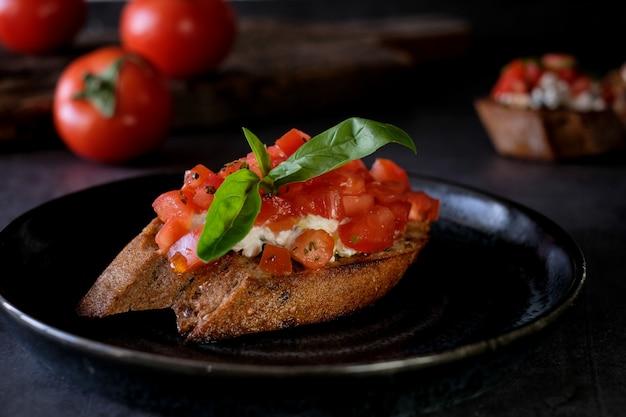 Брускетта с помидорами, базиликом и деревенским сыром на деревянной доске с помидорами таблицы. традиционная итальянская закуска или закуска Premium Фотографии