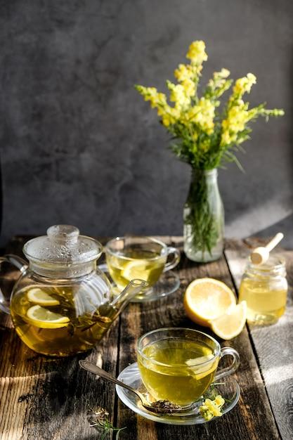 ガラスのカップとティーポットにレモンと蜂蜜入りハーブティー Premium写真