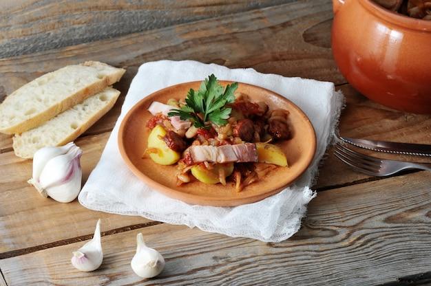 Рагу с картофелем, фасолью, копченое в глиняном горшочке Premium Фотографии