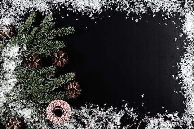 木の枝、コーンと雪でクリスマスの挨拶の背景 Premium写真