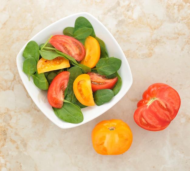 Салат с желтыми и красными помидорами и шпинатом Premium Фотографии