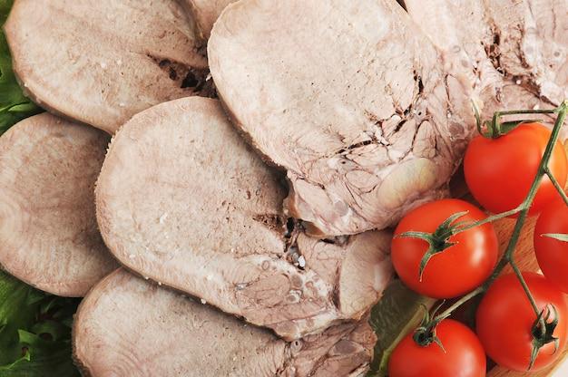 レタスの葉、チェリートマトの大皿に牛タン Premium写真
