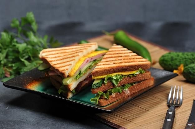 プレート上のハムとオムレツの三角形のサンドイッチ Premium写真