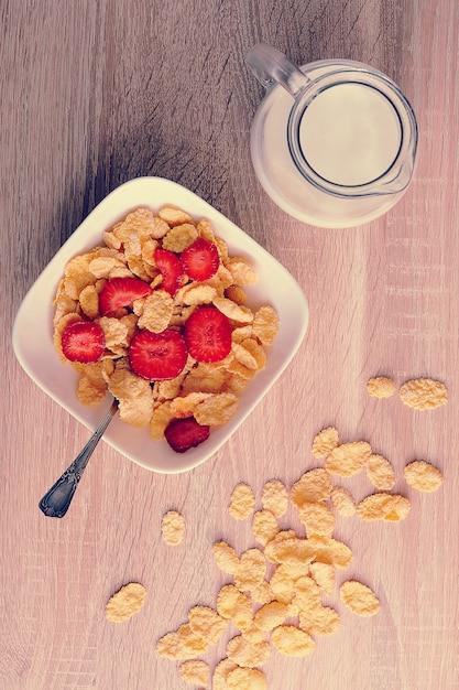 イチゴと木製の背景にミルクの水差しのコーンフレーク Premium写真