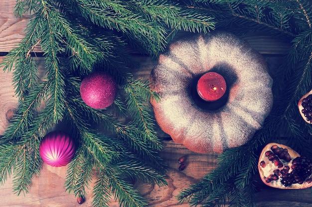Кекс со свечой, елкой и елочными украшениями на деревянном фоне Premium Фотографии