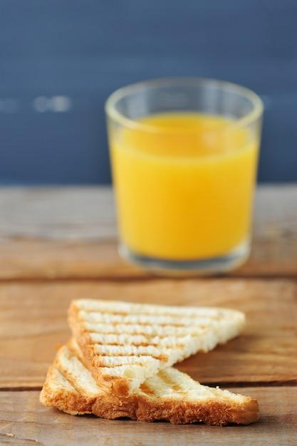 Два тостового хлеба крупным планом на стакан апельсинового сока Premium Фотографии