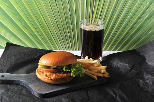 Круглый гамбургер с куриной котлетой и картофелем фри и стаканом кокса Premium Фотографии