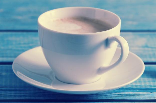 青いテーブルに白いマグカップのカプチーノ Premium写真