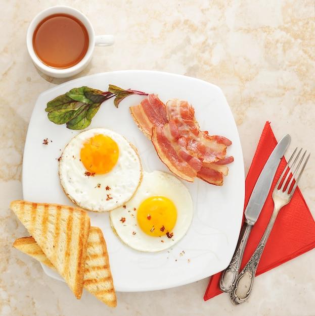 大理石の表面に目玉焼き、トースト、ベーコン、紅茶を添えた朝食 Premium写真
