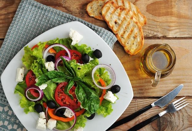 フェタチーズ、オリーブ、トマト、レタス、木製の表面にバジルのサラダ Premium写真