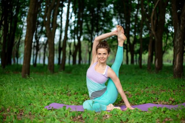 Худенькая брюнетка занимается спортом и выполняет красивые и сложные позы йоги в летнем парке Premium Фотографии