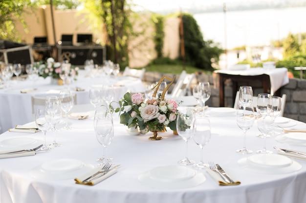 真ちゅう製の花瓶に生花で飾られた結婚式のテーブルセッティング。結婚式のフローリストリー。緑の自然の景色を望む屋外のゲスト用の宴会テーブル。バラ、トルコギキョウ、ユーカリの葉の花束。 Premium写真