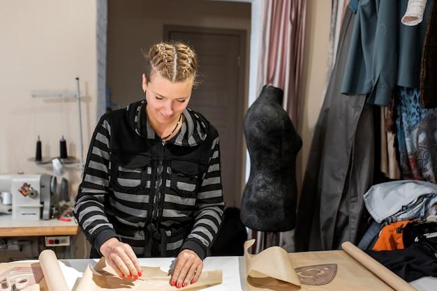 若い女の子のデザイナーの服は、パターンの紙を折った。オーダーメイドの服を作る、ファッションデザイナーのコンセプト Premium写真