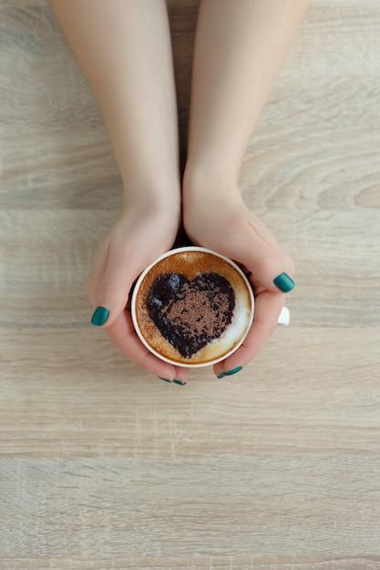 白いコーヒーカップを両手トップビュー。コーヒーにハートプリント Premium写真