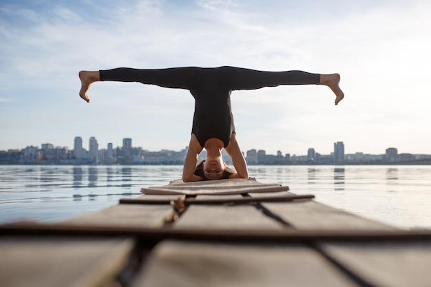 市と静かな木製の桟橋でヨガの練習の若い女性。都市ラッシュのスポーツとレクリエーション Premium写真