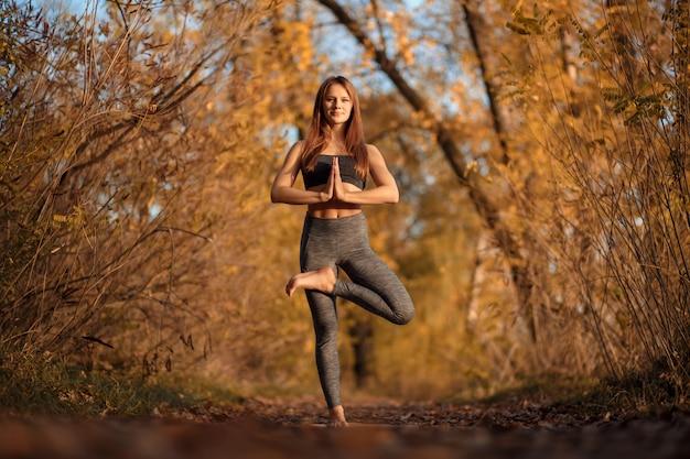 黄色の葉で秋の公園でヨガの練習の若い女性。スポーツとレクリエーションのライフスタイル Premium写真