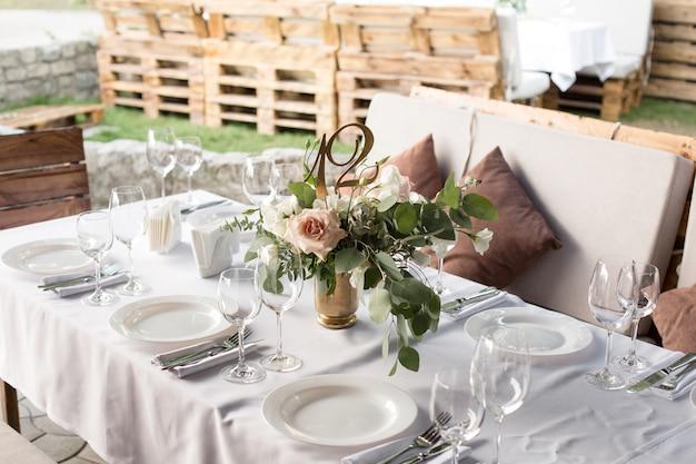 真ちゅう製の花瓶に生花で飾られた結婚式のテーブルセッティング。結婚式のフローリストリー。緑の自然の景色を望む屋外のゲスト用の宴会テーブル。バラ、トルコギキョウ、ユーカリの葉の花束 Premium写真